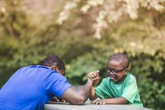 Father arm wrestling with son at parkland eco camp Stock Photos
