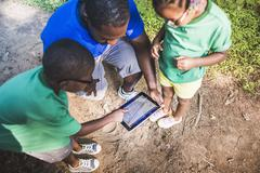 Father with daughter and son navigating with digital tablet at eco camp Stock Photos