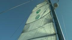 Descent mainsail on mast sailing catamaran. Stock Footage