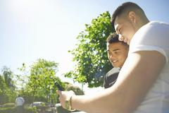 Two young adult friends looking at text message on smartphone Stock Photos
