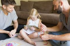 Male couple and daughter threading picture books on sitting room floor Stock Photos