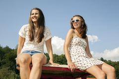Two young women sitting in trailer - stock photo
