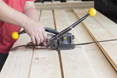 Close up of male warehouse worker fastening wooden planks in hardware store - stock photo
