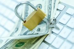 Security lock on dollar bills with white computer keyboard - stock photo