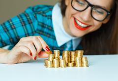 Smiling woman stacking gold coins into columns Kuvituskuvat