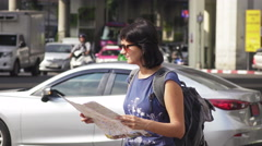 Attractive woman reading tourist map on city street Stock Footage