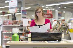 Female shop assistant checking orders in hardware store Stock Photos