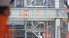 4K Team of engineers at power plant with 2 people shaking hands in foreground Stock Footage