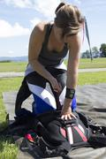 Female skydiver closing parachute container in field,  Buttwil, Luzern, Kuvituskuvat
