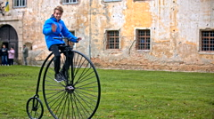 Boy waving from penny-farthing bicycle Stock Footage