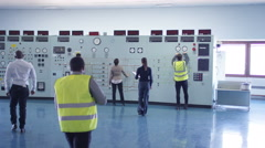 4KWorkers in power plant control room looking at control panel & checking system Stock Footage