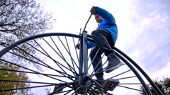 Boy trying to reach pedals on penny-farthing bicycle - stock footage