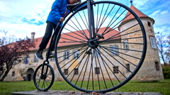Boy climb to penny-farthing bicycle statue Stock Footage