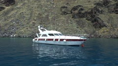 Motor yacht parked near a steep rocky shore. Stock Footage