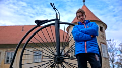 Boy posing with penny-farthing bicycle statue Stock Footage