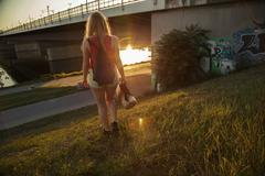 Rear view of young woman walking near bridge and riverside Stock Photos