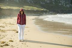 Mature woman strolling on beach with hands in pockets, Camaret-sur-mer, Stock Photos