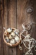 Raw quail eggs in a wooden bowl on wooden table. Stock Photos
