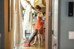 Young woman vacuuming with green cleaning products Stock Photos