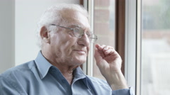 4K Portrait of sad elderly man sitting by the window.  Stock Footage