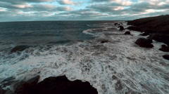 Aerial view of waves crashing on rocky beach - stock footage