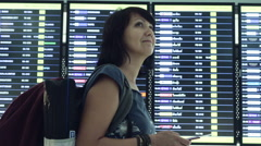 Woman Looking At Timetable Departure Board Stock Footage