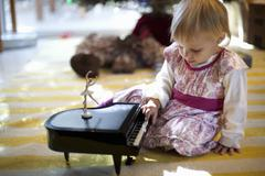 Female toddler sitting on living room floor playing with toy piano music box at Kuvituskuvat
