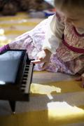Female toddler sitting on living room floor playing toy piano music box at Xmas Kuvituskuvat