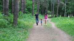 Mom and young daughter and dad, a young family on a walk in the park in summer - stock footage