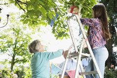 Grandparents and granddaughter hanging up bunting Stock Photos