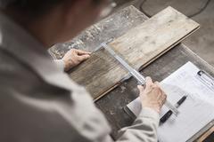 Carpenter measuring wood plank with vernier caliper in factory, Jiangsu, China - stock photo