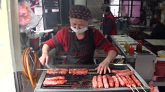 Asian woman cooking sausages Stock Footage