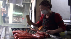 Asian woman cooking sausages on a plate and pouring sauce Stock Footage