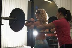 Crossfitter trainer coaching woman with barbell in gym Stock Photos