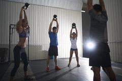 Crossfitters working out with kettlebell in group class Stock Photos