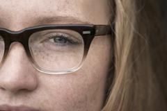 Close-up of young woman with freckles wearing eye glasses Stock Photos