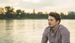 Young man wearing checked shirt by lake - stock photo