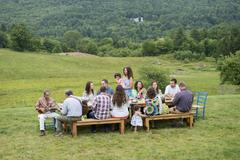Family having meal together and socialising, outdoors Stock Photos