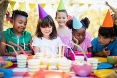 Cute children looking candles during a birthday party - stock photo