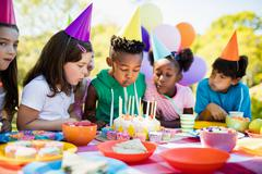 Cute children blowing together on the candle during a birthday party - stock photo