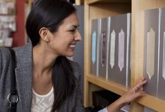 Female customer browsing files in stationery shop - stock photo