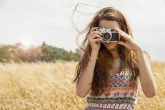Young woman taking photo with vintage camera in field Stock Photos