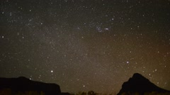 Stars shimmer in night sky as clouds gradually obscure view - stock footage