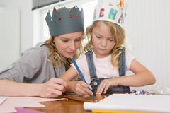 Mother and daughter making paper crowns Stock Photos