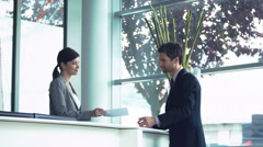 Hotel receptionist handing document to customer - stock footage