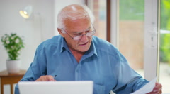 4K Frustrated senior man working on a laptop computer & looking at paperwork.  Stock Footage