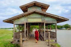 Amarapura, Myanmar - 28 June, 2015: Buddhist monk walks on wooden U Bein brid Stock Photos