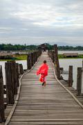 Amarapura, Myanmar - 28 June, 2015: Young monk walks on wooden U Bein bridge  Stock Photos