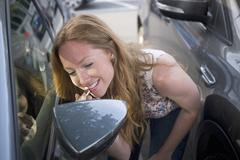 Young woman applying lipstick whilst looking in car wind mirror Kuvituskuvat