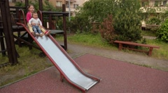 Two little cute girls having great fun while riding down slide in the playground Stock Footage